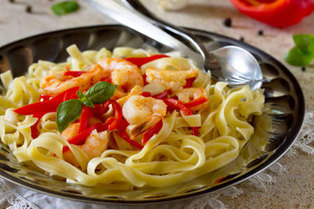 Italian pasta tagliatelle with shrimp and sweet peppers paprika, decorated with basil on a stone background.