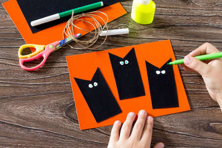 halloween black cat: The child create a greeting card Halloween black cat out of paper, drawing paper parts. Glue, scissors, leaves velvet paper on a wooden table. Childrens art project, a craft for children.