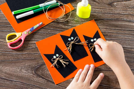 halloween black cat: The child create a greeting card Halloween black cat out of paper, glues the paper parts. Glue, scissors, leaves velvet paper on a wooden table. Childrens art project, a craft for children.