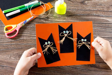 The child create a greeting card Halloween black cat out of paper. Glue, scissors, leaves velvet paper on a wooden table. Childrens art project, a craft for children. Stock Photo