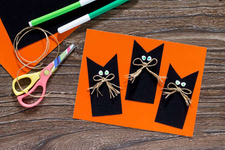 The child create a greeting card Halloween black cat out of paper. Glue, scissors, leaves velvet paper on a wooden table. Children's art project, a craft for children. Standard-Bild