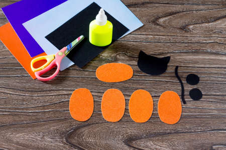 The child create a birthday card for Halloween paper black cat in pumpkin. Glue, scissors, leaves velvet paper on a wooden table. Children's art project, a craft for children.