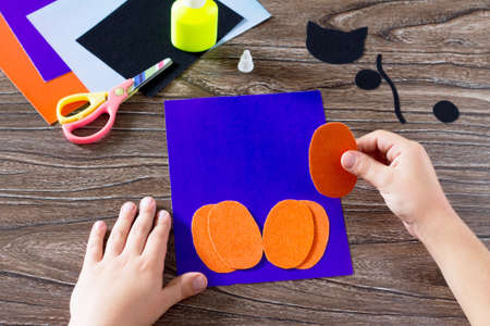The child create a greeting card Halloween paper black cat in pumpkin, pasting paper parts. Glue, scissors, leaves velvet paper on a wooden table. Children's art project, a craft for children.