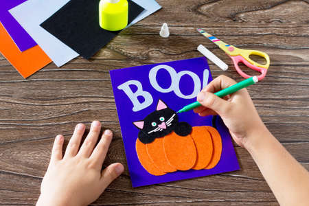The child create a greeting card Halloween paper black cat in pumpkin, paints, paper parts. Glue, scissors, leaves velvet paper on a wooden table. Children's art project, a craft for children. Stockfoto