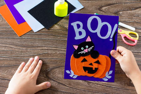 The child create a birthday card for Halloween paper black cat in pumpkin. Glue, scissors, leaves velvet paper on a wooden table. Childrens art project, a craft for children.