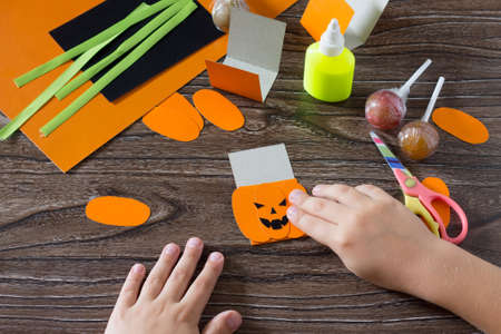 The child create a greeting packaging for lollipop on Halloween pumpkin paper, be glued for paper the details. Children's art project, a craft for children.