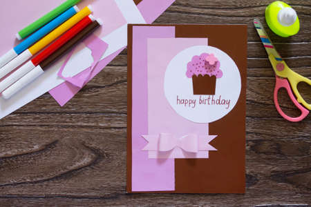 hobbies: Greeting card handmade birthday inscription is that on his birthday. Sheets of paper, glue, scissors on a wooden table. Childrens art project, a craft for children.