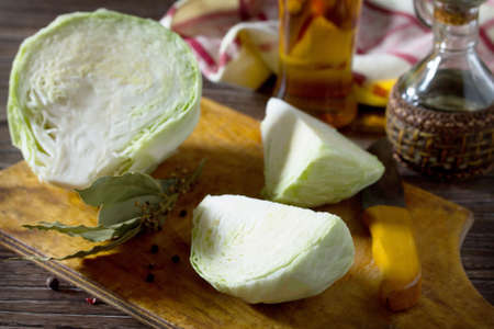 Sliced ??cabbage and vinegar, oil on old wooden table. In order to prepare a salad. Healthy food concept. Stock Photo