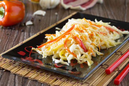 korean salad: Korean salad of cabbage, carrots, sweet peppers - kimchi in an Asian style on a wooden table. Stock Photo