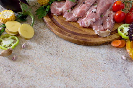 pork tenderloin: Fresh raw meat pork tenderloin with vegetables on a cutting board. Stone background. Copy space. Stock Photo