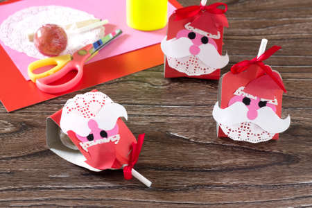 The child create a greeting packaging for candy Santa Claus on paper. Childrens art project, a craft for children.