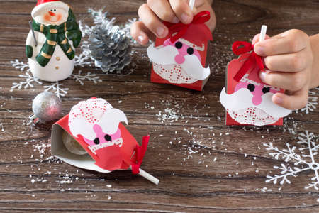 The child create a greeting packaging for candy Santa Claus on paper. Children's art project, a craft for children.