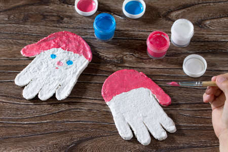 Child paints acrylic paints Christmas toy from the salty test frost grandfather. Children's art project, a craft for children.