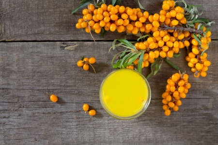 seabuckthorn: Autumn hot drink. Tea with sea-buckthorn berries branch on vintage wooden background. Space for your text. Stock Photo