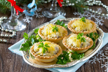 Holiday appetizer: tartlets with mushrooms and meat on a celebratory Christmas background.