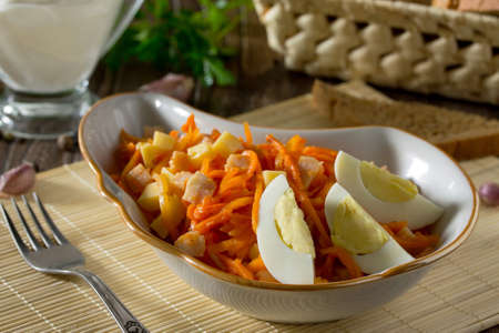 korean salad: Salad of carrots in Korean, with cheese, egg and chicken meat on a wooden background. Stock Photo