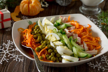 korean salad: Festive salad for the Christmas table: carrots in Korean with green peas, cucumber, egg and meat. Stock Photo