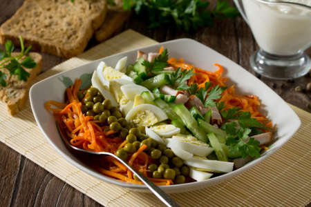 korean salad: Salad of carrots in Korean with green peas, cucumber, egg and chicken meat on a wooden background.