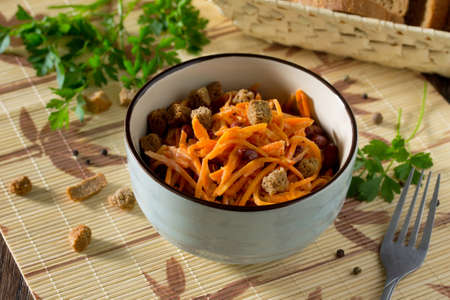 christmas cracker: Salad of carrots in Korean with red beans, garlic and croutons on wooden background. Stock Photo
