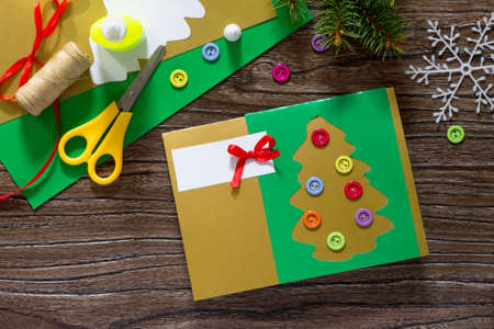 stock photo the child create christmas greeting cards paper festive fir in christmas tree toys glue scissors paper leaves thread on a wooden table - Create Christmas Cards