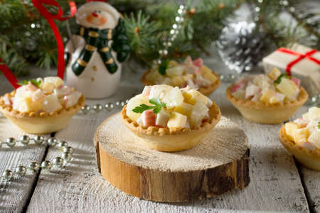 Holiday hors doeuvre: tartlets with crab sticks, cheese and pineapple on a celebratory Christmas background. Stock Photo