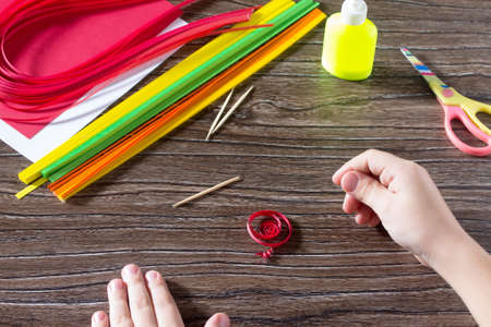 cuisine entertainment: The child create greeting cards origami paper honey and garnet tree branch on a wooden table. Manufacture of paper origami grenades. Of the Jewish New Year celebration, Rosh Hashana.