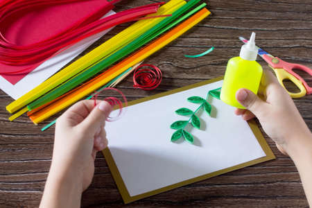 cuisine entertainment: The child create greeting cards origami paper honey and garnet tree branch on a wooden table. Making of paper strips pomegranate tree. Of the Jewish New Year celebration, Rosh Hashana.