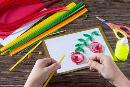 cuisine entertainment: The child create greeting cards origami paper honey and garnet tree branch on a wooden table. Making of paper strips honey. Of the Jewish New Year celebration, Rosh Hashana.