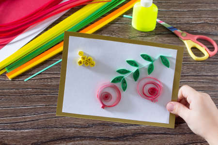 cuisine entertainment: The child create greeting cards origami paper honey and garnet tree branch on a wooden table. Of the Jewish New Year celebration, Rosh Hashana and Tu BShvat. Stock Photo