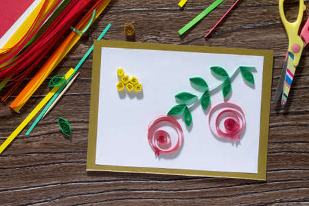 The child create greeting cards origami paper honey and garnet tree branch on a wooden table. Of the Jewish New Year celebration, Rosh Hashana and Tu BShvat. Stock Photo
