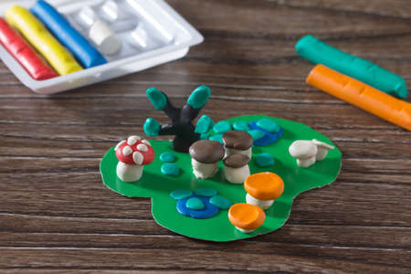 Consumables: Child sculpts plasticine mushrooms tree and autumn leaves. Consumables for kids arts and crafts on a wooden table. Plasticine idea for children. Activities in the kindergarten and at home.