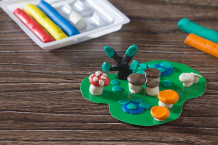 Consumables: Card plasticine mushroom, tree and autumn leaves. Consumables for kids arts and crafts on a wooden table. The concept of childrens activities in the kindergarten and at home. Stock Photo