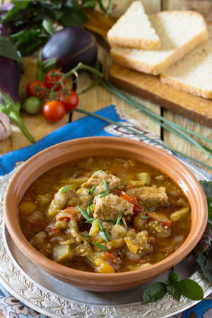 Traditional Georgian hot ragout with meat and vegetables (eggplant, peppers, tomatoes). Beef goulash. Healthy food concept. Stock Photo