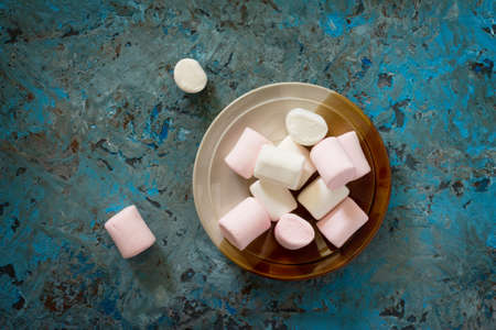 White and pink marshmallows in a ceramic bowl on blue concrete background. Top view.