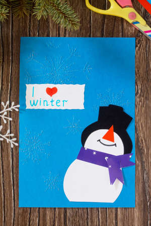The child makes a greeting card with a snowman. Glue, paper, scissors on a wooden table. Childrens art project, a craft for children.