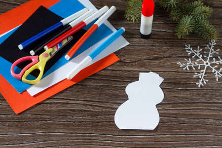 The child cut paper details snowman. The child makes a greeting card with a snowman. Glue, paper, scissors on a wooden table. Childrens art project, a craft for children.