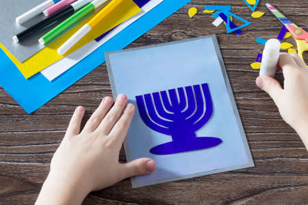 jewish home: The child glues the the details greeting cards image of the Jewish holiday of Hanukkah. Glue, scissors, paper, leaves on wooden table. Childrens Art Project, needlework, crafts for children.