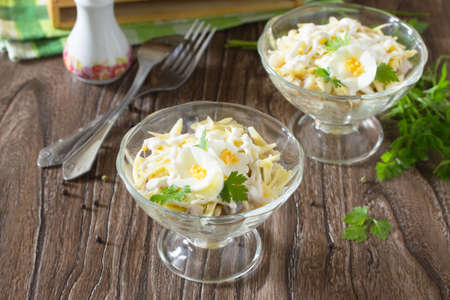 Festive salad with pickled herring, cheese and egg. Appetizer on the table Christmas or New Year. Stock Photo