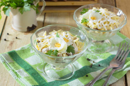 Salad with pickled herring, cheese and egg. Appetizer on a festive table, Easter or birthday.