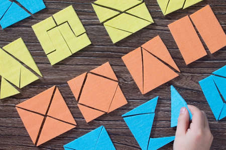 Hand the kid keeps missing part in the Tangram puzzle square wooden table above. The concept of early child development. Stock Photo