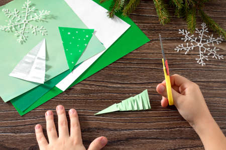 The child makes paper fir tree. Scissors, paper on a wooden table. Children's art project, a craft for children. Stockfoto