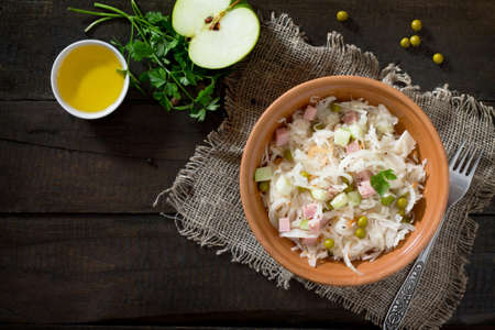 Salad with sauerkraut, ham, apple and green peas. Snack on a festive table. Top view.