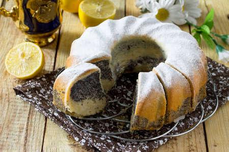 Traditional homemade lemon cake with poppy filling. Dessert birthday or Easter on vintage wooden background.