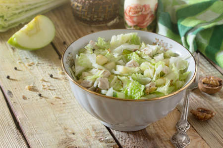 Salad with cabbage, chicken, apple, cucumber and walnuts. Snack on a festive table.