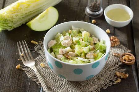 Salad with cabbage, chicken, apple, cucumber and walnuts. Healthy food concept.