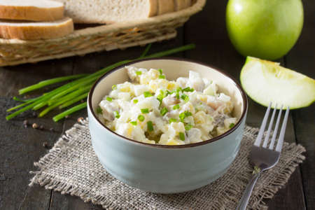 Salad with herring, eggs, apples and potatoes. Snack on a festive table on a wooden table.