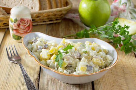 Salad with herring, eggs, apples and potatoes. Snack on a festive table.