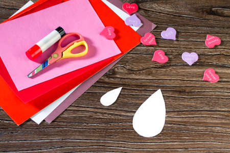 i like my school: Childrens greeting card Two birds and heart from a paper on Valentines Day. Sheets of paper, glue, scissors on a wooden table. Childrens art project, a craft for children. Made by hand. Stock Photo