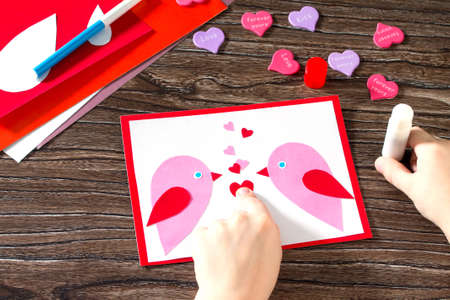 i like my school: The child glues the details applique. Baby greeting card for Valentines Day. Sheets of paper, glue, scissors on a wooden table. Childrens art project, a craft for children. Stock Photo