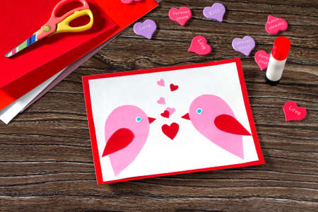 i like my school: Childrens greeting card Two birds and heart from a paper on Valentines Day. Childrens art project, a craft for children. Made by hand.